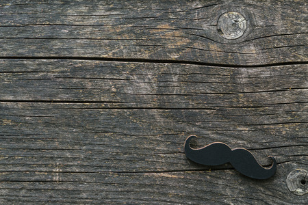 male face: Fake black mustache on wooden background. Stock Photo