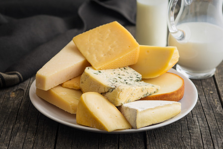 Different kinds of cheeses on old wooden table.
