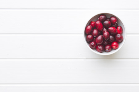 vaccinium macrocarpon: The tasty american cranberry in bowl on white table.