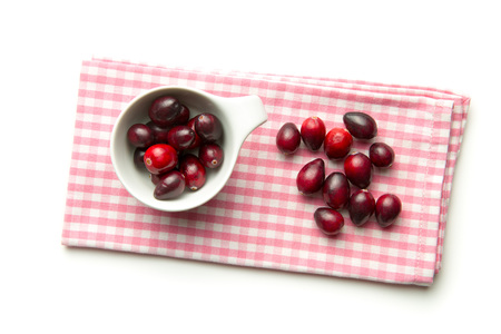vaccinium macrocarpon: The tasty american cranberries in bowl on checkered napkin.