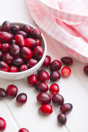 vaccinium macrocarpon: The tasty american cranberries in bowl on white table.
