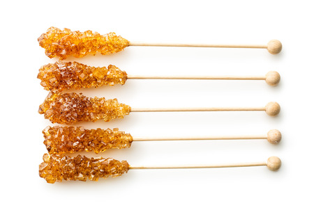 Brown amber sugar crystal on wooden stick isolated on white background.