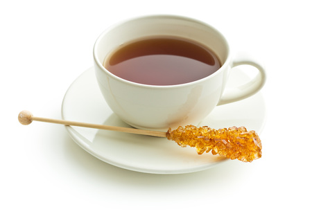 wooden stick: Brown amber sugar crystal on wooden stick and cup of tea isolated on white background.