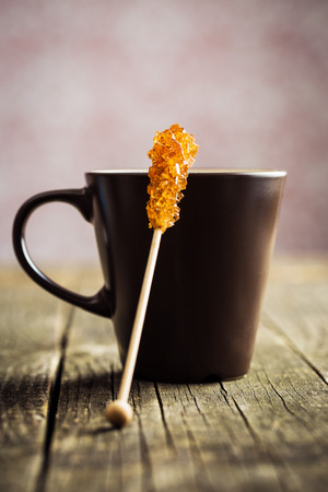 Brown amber sugar crystal on wooden stick and coffee cup on old wooden table. Stock Photo