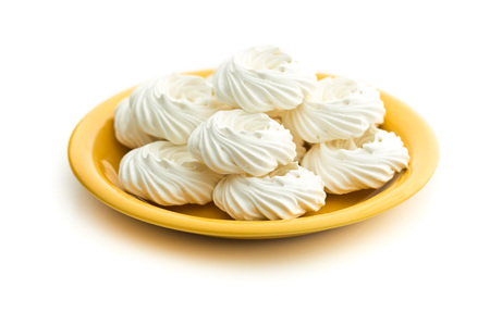 Sweet white meringue on plate isolated on white background.