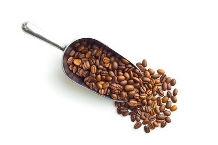 Granos de café en la cucharada del metal aislada en el fondo blanco. Vista superior.