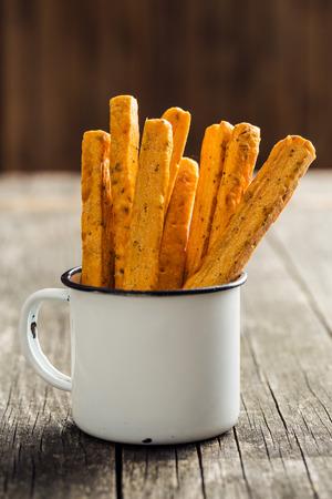 Crispy bread sticks in old cup.
