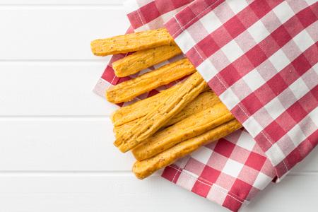 caloric: Crispy bread sticks on checkered napkin.
