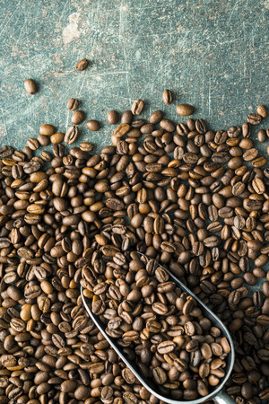 coffee beans: Roasted coffee beans and metal scoop.