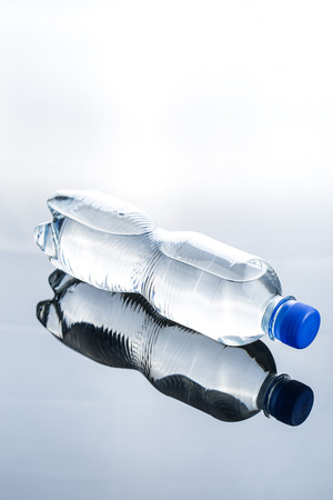 Small plastic water bottle on mirror table. Stock Photo