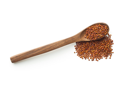 red quinoa: Red quinoa seeds in wooden spoon isolated on white background. Top view.