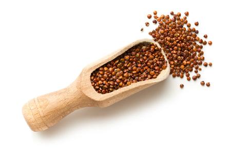 Graines de quinoa rouge dans une boule en bois isolé sur fond blanc. Vue de dessus