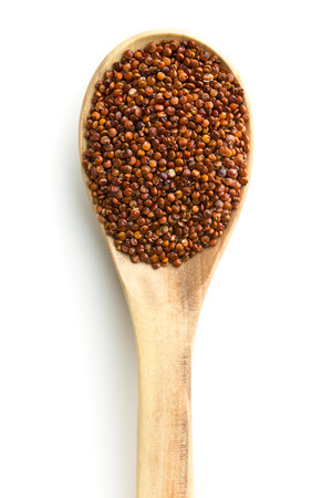 Red quinoa seeds in wooden spoon isolated on white background. Top view.