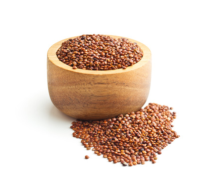 Red quinoa seeds in wooden bowl isolated on white background.