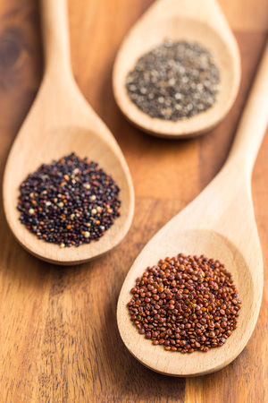 protein crops: Red and black quinoa and chia seeds in wooden spoon.