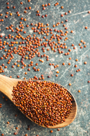 red quinoa: Red quinoa seeds in wooden spoon. Stock Photo