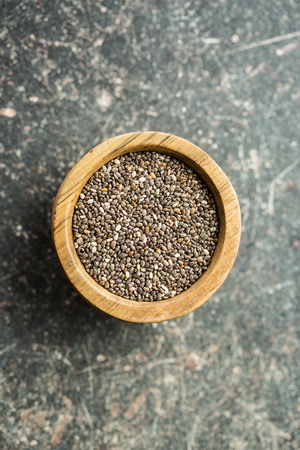 Superfood. Chia seeds in wooden bowl on old table. Top view.