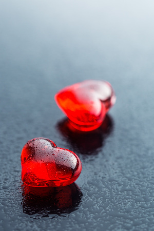Dewy red hearts on black table. Stock Photo