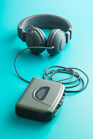 The vintage audio player and headphones on blue background. Stock Photo
