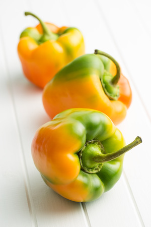 Multicolored bell pepper on white table.
