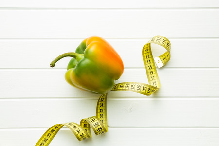 Multicolored bell pepper with measuring tape. Top view. Stock Photo