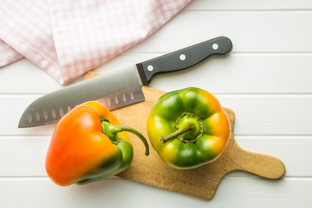 Multicolored bell pepper with knife on cutting board. Top view.