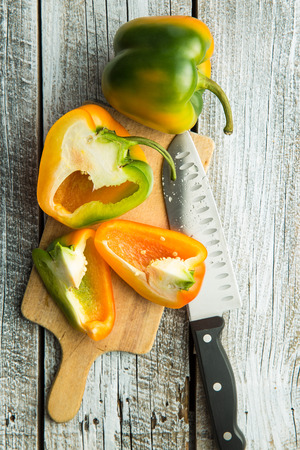 bell peper: Multicolored bell pepper with knife on cutting board. Top view.