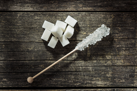 crystallized: Crystallized sugar on wooden stick and sugar cube.