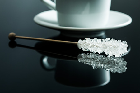 crystallized: Crystallized sugar on wooden stick on black table.