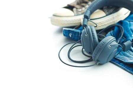 stereo cut: Headphones and blue jeans isolated on white background.
