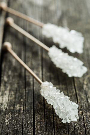 crystallized: Crystallized sugar on wooden stick on wooden table.