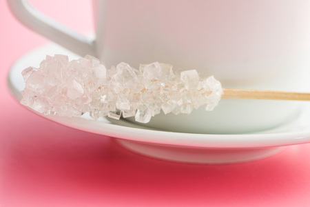 crystallized: Crystallized sugar on wooden stick on pink background.