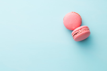 Tasty sweet macarons. Macaroons on blue background. Top view. Stock Photo