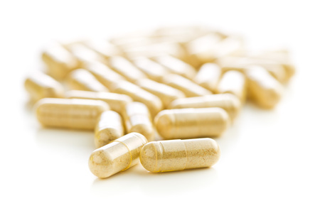Le capsule gialle isolate su sfondo bianco. Archivio Fotografico - 71762127