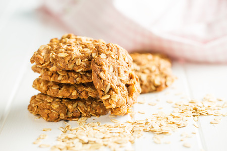 Homemade oatmeal cookies on white wooden table.