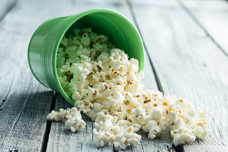 The salty popcorn on old wooden table. Stock Photo