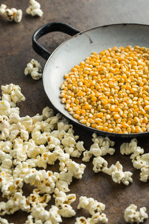 Popcorn and corn seeds on rusty background.