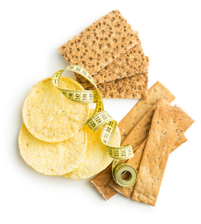 galletas integrales: The healthy crispbread with measuring tape isolated on white background. Foto de archivo