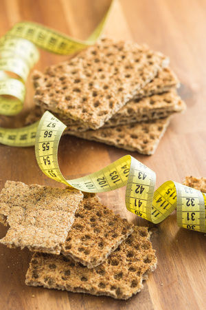 Healthy crispbread and measuring tape on wooden table.