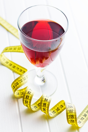Glass of red wine and measuring tape. Diet concept. Stock Photo