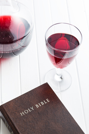 roses and blood: Glass of red wine with holy bible. Stock Photo