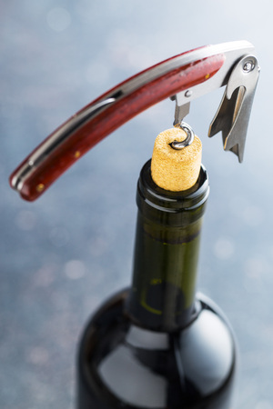 uncork: Bottle of wine with corkscrew. Stock Photo
