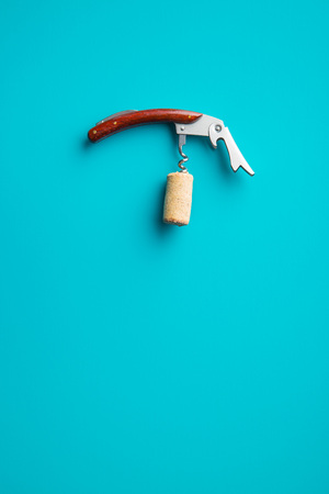 Cork and corkscrew blue background.
