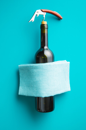 Bottle of wine with corkscrew on blue background. Top view. Stock Photo