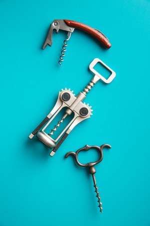 Various types of corkscrews on blue background. Stock Photo