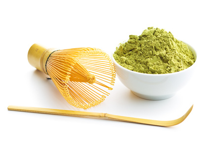 Green matcha tea powder and bamboo whisk and spoon isolated on white background. Stock Photo