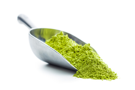Green matcha tea powder in scoop isolated on white background. Stock Photo