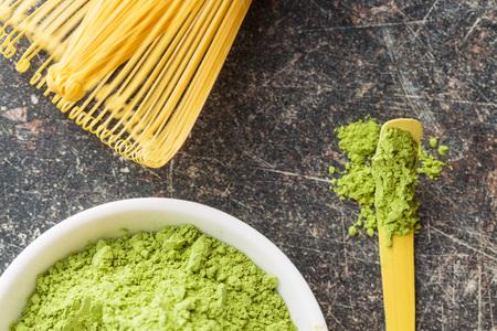 maccha: Green matcha tea powder, spoon and bamboo whisk. Top view. Stock Photo