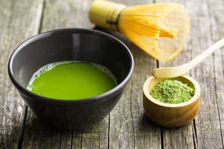 Green matcha tea , bamboo whisk, spoon and tea powder.