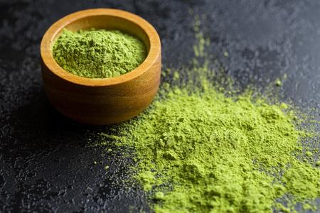 maccha: Green matcha tea powder in bowl. Stock Photo